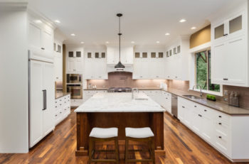 Kitchen Interior with Island, Hardwood Floors, and Pendant Lights in New Luxury Home
